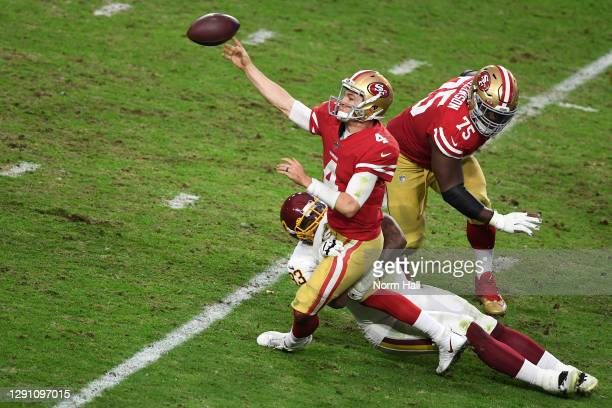 Quarterback Nick Mullens of the San Francisco 49ers attempts a pass as he is tackled by defensive tackle Jonathan Allen of the Washington Football...