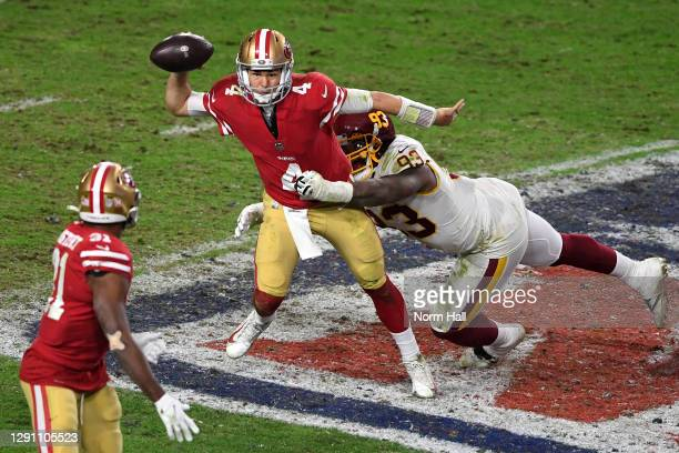 Quarterback Nick Mullens of the San Francisco 49ers attempts to deliver a pass as he is tackled by defensive tackle Jonathan Allen of the Washington...