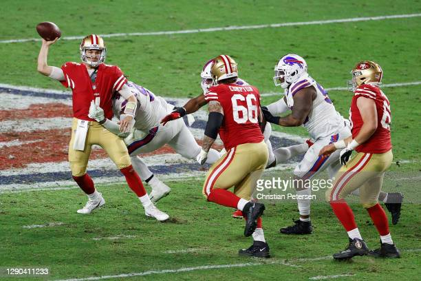 Quarterback Nick Mullens of the San Francisco 49ers avoids a tackle from defensive tackle Vernon Butler of the Buffalo Bills during the NFL game at...
