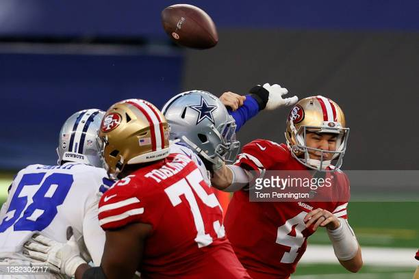 Quarterback Nick Mullens of the San Francisco 49ers has the ball knocked away by the Dallas Cowboys during the fourth quarter at AT&T Stadium on...
