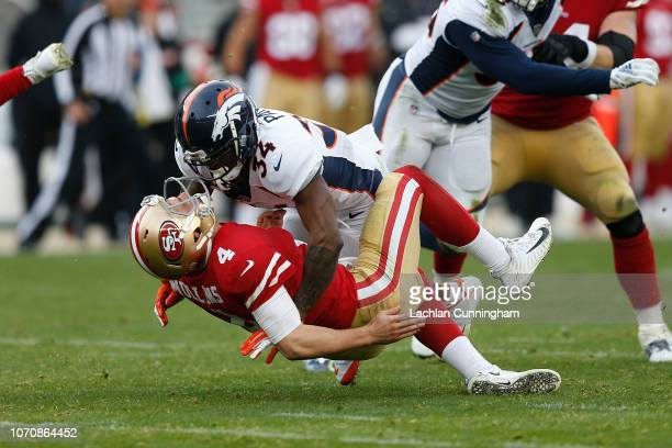 Quarterback Nick Mullens of the San Francisco 49ers is tackled by Will Parks of the Denver Broncos at Levi's Stadium on December 9 2018 in Santa...