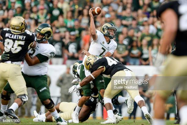 Quarterback Nick Stevens of the Colorado State Rams is hit by linebacker Jacob Callier of the Colorado Buffaloes as he passes in the first half at...