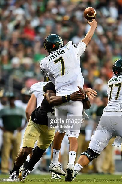 Quarterback Nick Stevens of the Colorado State Rams is hit by linebacker Kenneth Olugbode of the Colorado Buffaloes as he passes at Sports Authority...
