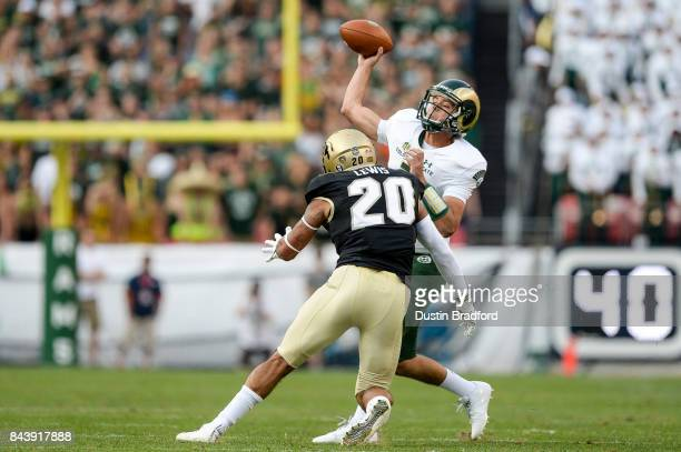 Quarterback Nick Stevens of the Colorado State Rams is pressured by linebacker Drew Lewis of the Colorado Buffaloes at Sports Authority Field at Mile...