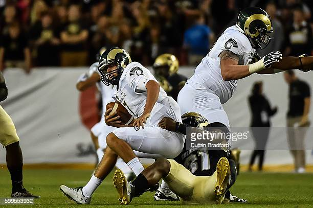 Quarterback Nick Stevens of the Colorado State Rams is sacked by linebacker Kenneth Olugbode of the Colorado Buffaloes at Sports Authority Field at...