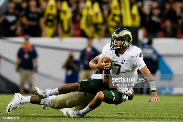 Quarterback Nick Stevens of the Colorado State Rams is sacked by linebacker Jacob Callier of the Colorado Buffaloes in the first half of a game...