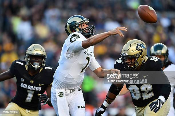 Quarterback Nick Stevens of the Colorado State Rams passes against the Colorado Buffaloes under pressure from defensive end Jordan Carrell in the...