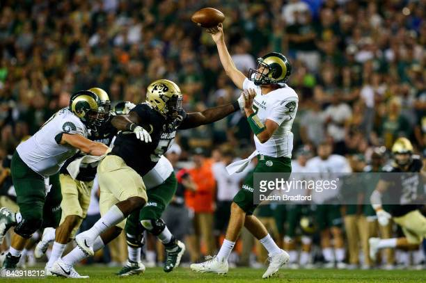 Quarterback Nick Stevens of the Colorado State Rams passes under pressure by defensive end Leo Jackson III of the Colorado Buffaloes at Sports...