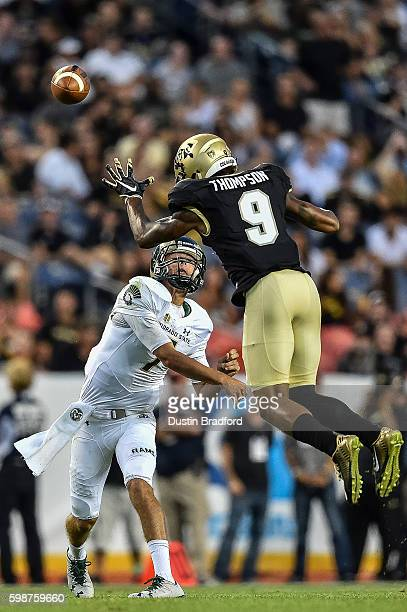 Quarterback Nick Stevens of the Colorado State Rams throws as defensive back Tedric Thompson of the Colorado Buffaloes defends at Sports Authority...