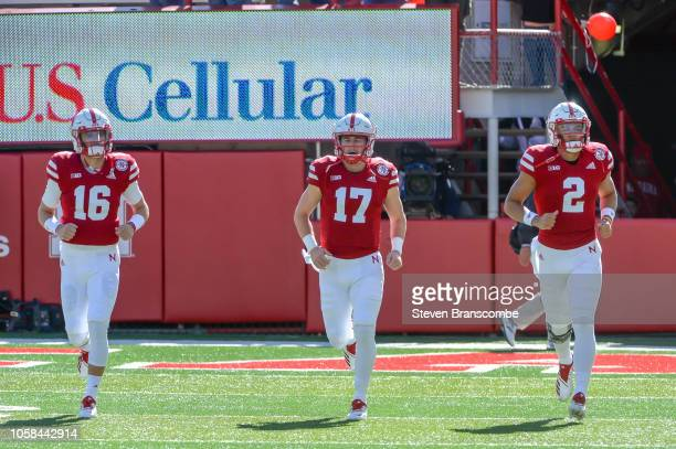 Quarterback Noah Vedral of the Nebraska Cornhuskers and quarterback Andrew Bunch and quarterback Adrian Martinez warm up before the game against the...