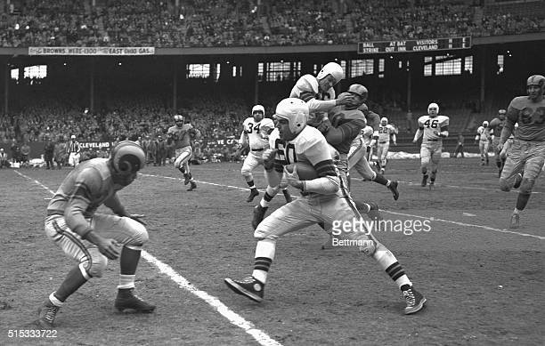 Quarterback Otto Graham, of the Browns, one of the top passers in football, picks up 12 yards by the overland route as he carries the ball himself in...