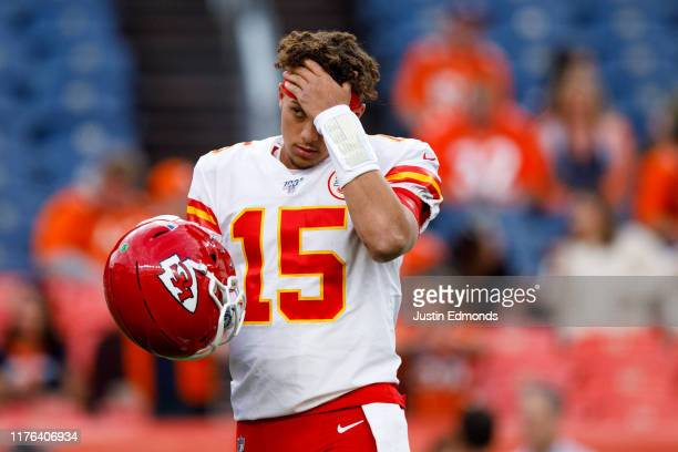 Quarterback Patrick Mahomes of the Kansas City Chiefs adjusts his hair on the field before a game against the Denver Broncos at Empower Field at Mile...