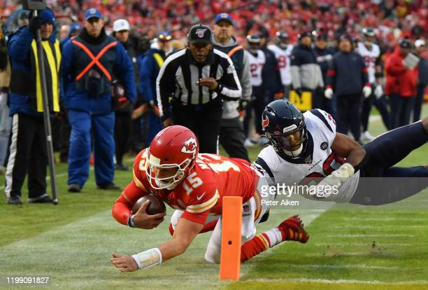 Quarterback Patrick Mahomes of the Kansas City Chiefs dives to the 1yard line for a first down over Justin Reid of the Houston Texans in the third...