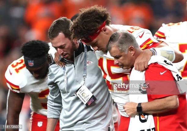 Quarterback Patrick Mahomes of the Kansas City Chiefs is escorted off the field after an injury in the first half against the Denver Broncos in the...