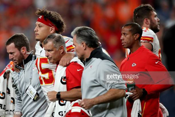 Quarterback Patrick Mahomes of the Kansas City Chiefs is escorted off the field after an injury on the first half against the Denver Broncos in the...