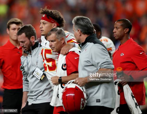 Quarterback Patrick Mahomes of the Kansas City Chiefs is escorted offs the field after an injury on the first half against the Denver Broncos in the...