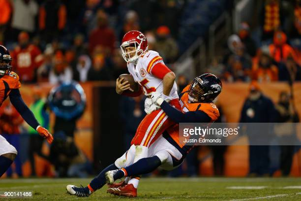 Quarterback Patrick Mahomes of the Kansas City Chiefs is sacked by defensive end DeMarcus Walker of the Denver Broncos during the fourth quarter at...