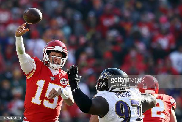 Quarterback Patrick Mahomes of the Kansas City Chiefs passes as defensive tackle Michael Pierce of the Baltimore Ravens defends during the game at...