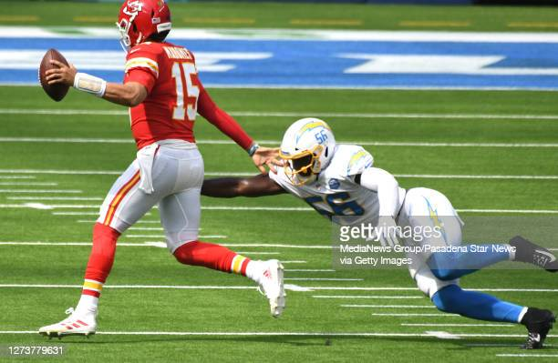 quarterback Patrick Mahomes of the Kansas City Chiefs scrambles as linebacker Kenneth Murray of the Los Angeles Chargers reaches for the tackle in...