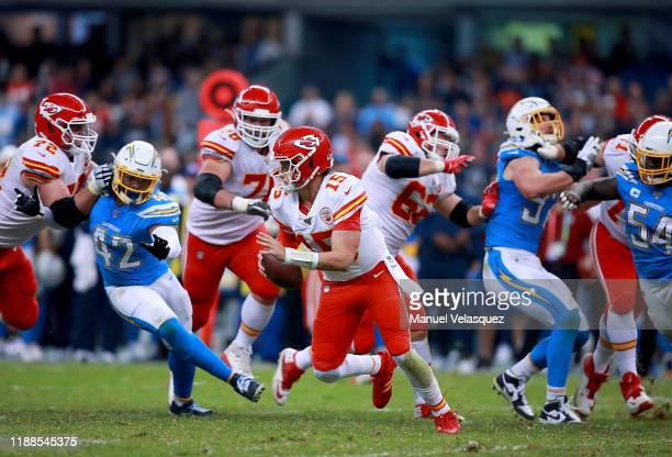 Quarterback Patrick Mahomes of the Kansas City Chiefs scrambles against the defense of the Los Angeles Chargers during the game at Estadio Azteca on...