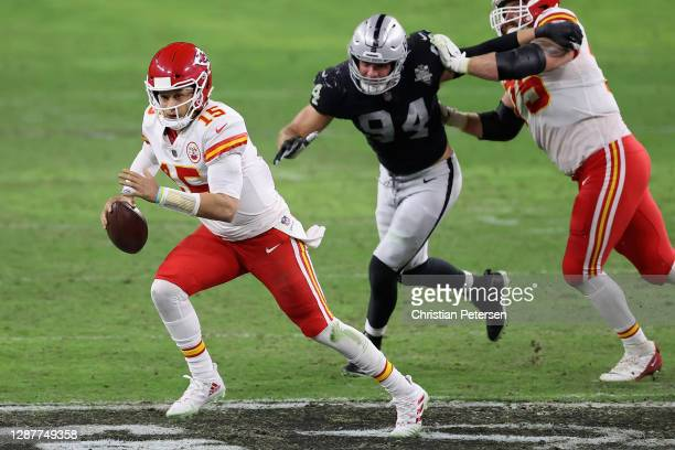 Quarterback Patrick Mahomes of the Kansas City Chiefs scrambles with the ball past defensive end Carl Nassib of the Las Vegas Raiders during the NFL...