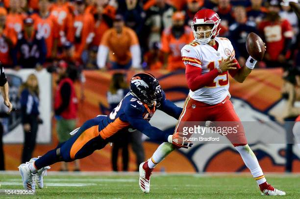 Quarterback Patrick Mahomes of the Kansas City Chiefs throws a lefthanded pass for a completion while he is hit by linebacker Von Miller of the...