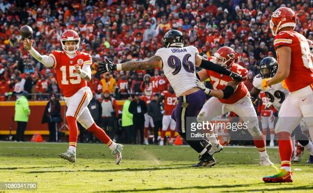 Quarterback Patrick Mahomes of the Kansas City Chiefs throws a pass around the pressure of defensive end Brent Urban of the Baltimore Ravens at...