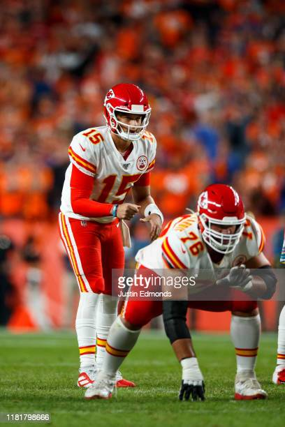 Quarterback Patrick Mahomes of the Kansas City Chiefs waits to snap the ball as guard Laurent DuvernayTardif blocks against the Denver Broncos during...