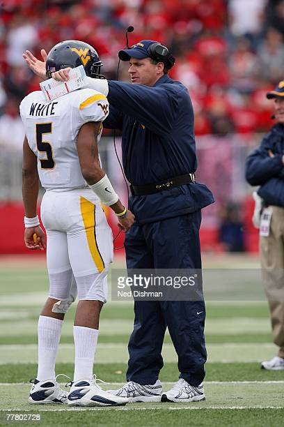 Quarterback Patrick White and head coach Rich Rodriguez of the West Virginia Mountaineers speak on the sideline against the Rutgers University...