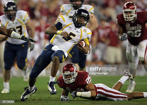 Quarterback Patrick White of the West Virginia Mountaineers runs for seven-yards past D.J. Wolfe of the Oklahoma Sooners in the second half at the...