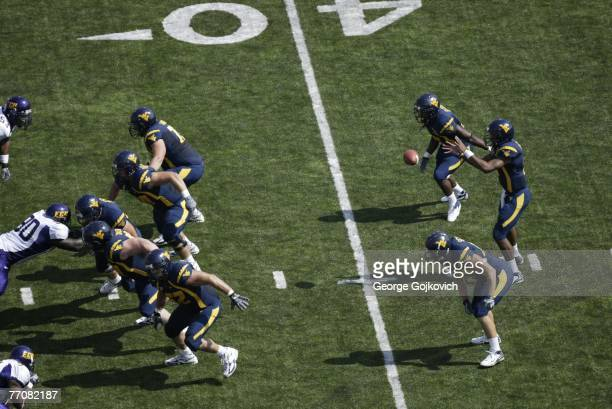 Quarterback Patrick White of the West Virginia University Mountaineers takes the snap from center while flanked by running back Steve Slaton and...