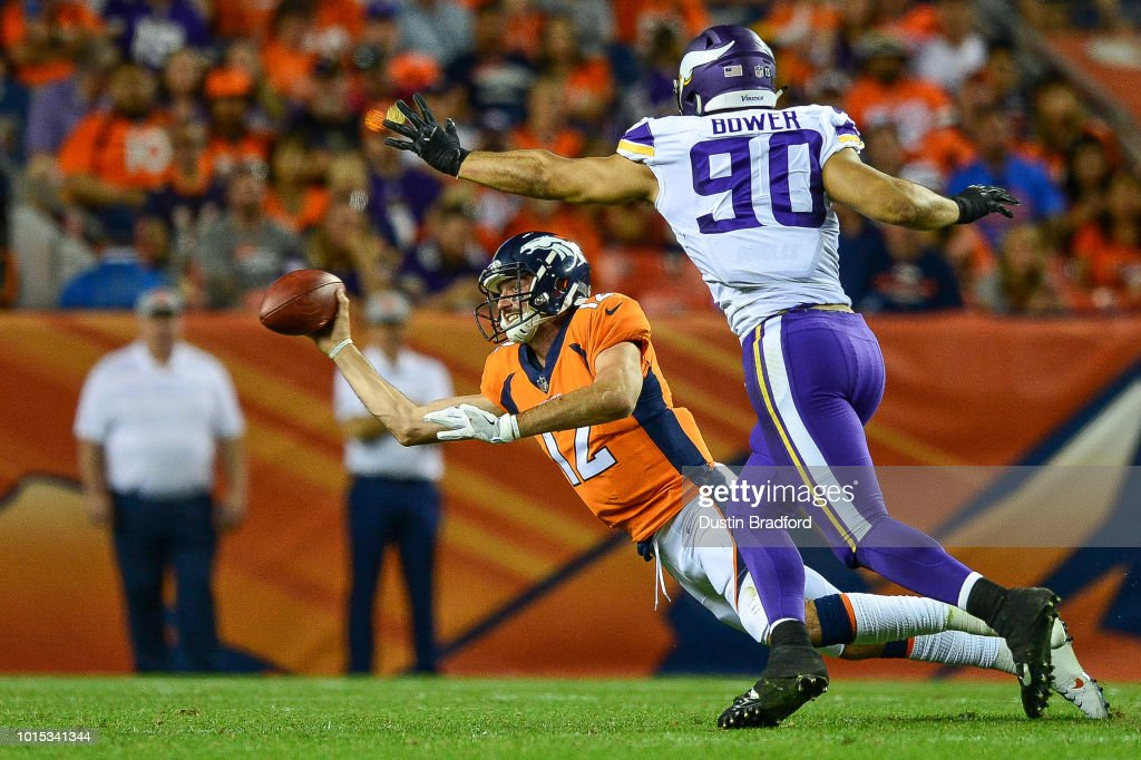 Quarterback Paxton Lynch #12 of the Denver Broncos throws the ball as he is tackled and covered by defensive end Tashawn Bower #90 of the Minnesota Vikings in the second quarter during an NFL preseason game at Broncos Stadium at Mile High on August 11, 2018 in Denver, Colorado.