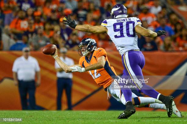 Quarterback Paxton Lynch of the Denver Broncos throws the ball as he is tackled and covered by defensive end Tashawn Bower of the Minnesota Vikings...