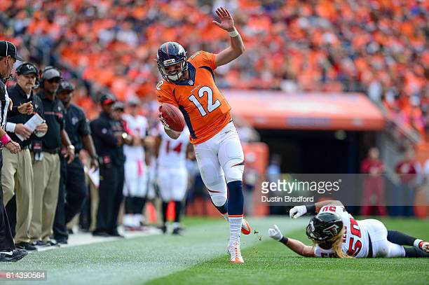 Quarterback Paxton Lynch of the Denver Broncos works for yards after breaking free from a tackle attempt by linebacker AJ Hawk of the Atlanta Falcons...