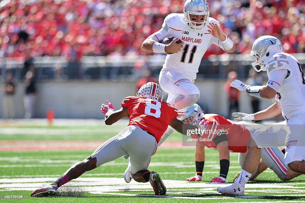 Quarterback Perry Hills #11 of the Maryland Terrapins leaps over Gareon Conley #8 of the Ohio State Buckeyes to pick up a first down in the third quarter at Ohio Stadium on October 10, 2015 in Columbus, Ohio. Ohio State defeated Maryland 49-28.