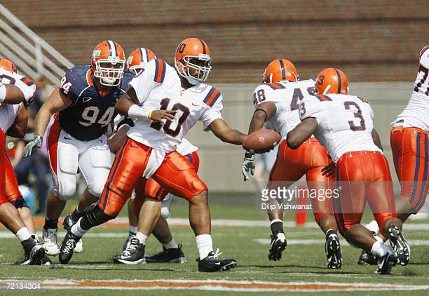 Quarterback Perry Patterson Jr. #10 of the Syracuse Orangemen hands-off the ball to Delone Carter against the Illinois Fighting Illini on September...