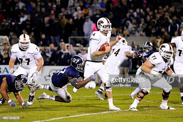 Quarterback Pete Thomas of the Louisiana Monroe Warhawks is pulled down by linebacker Antwione Williams of the Georgia Southern Eagles during the...