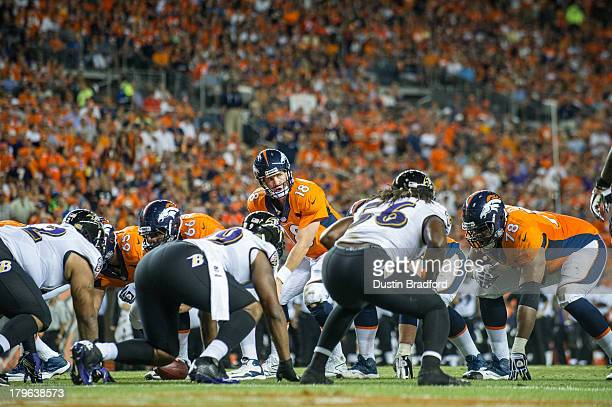 Quarterback Peyton Manning of the Denver Broncos audibles at the line of scrimmage against the Baltimore Ravens during the game at Sports Authority...
