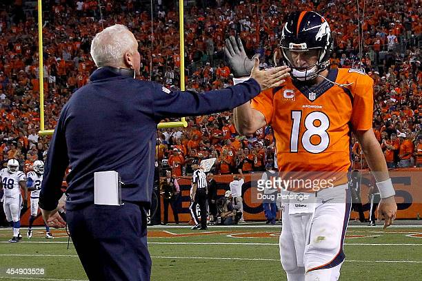 Quarterback Peyton Manning of the Denver Broncos celebrates his five yard touchdown pass to tight end Julius Thomas with head coach John Fox of the...