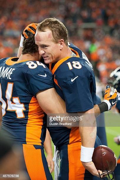 Quarterback Peyton Manning of the Denver Broncos celebrates his recordbreaking 509th career touchdown pass on the sideline with tight end Jacob Tamme...