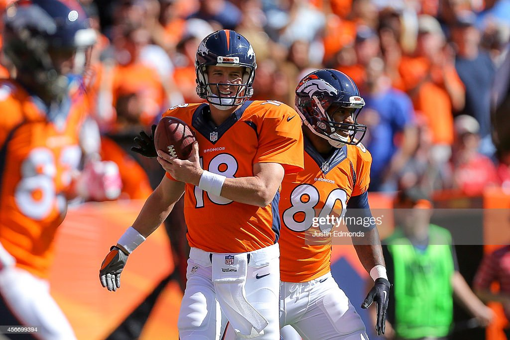 Quarterback Peyton Manning #18 of the Denver Broncos celebrates with Julius Thomas #80 after passing his 500th career touchdown pass Thomas in the first quarter of a game against the Arizona Cardinals at Sports Authority Field at Mile High on October 5, 2014 in Denver, Colorado.