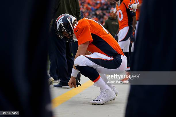 Quarterback Peyton Manning of the Denver Broncos crouches on the sidelines during a game against the Kansas City Chiefs at Sports Authority Field...
