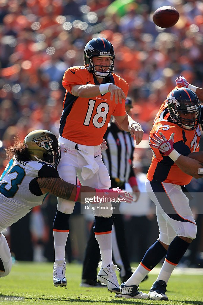 Quarterback Peyton Manning #18 of the Denver Broncos delivers a pass and is hit by defensive end Tyson Alualu #93 of the Jacksonville Jaguars at Sports Authority Field at Mile High on October 13, 2013 in Denver, Colorado. The Broncos defeated the Jaguars 35-19.