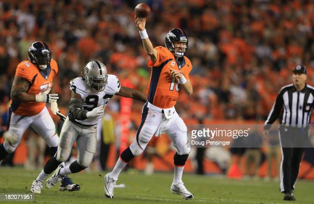 Quarterback Peyton Manning of the Denver Broncos delivers while under pursuit from Jason Hunter of the Oakland Raiders and Orlando Franklin of the...