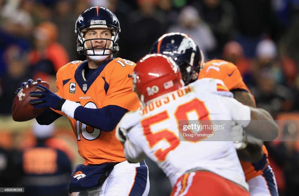 Quarterback Peyton Manning #18 of the Denver Broncos drops back to pass as tackle Orlando Franklin #74 of the Denver Broncos blocks outside linebacker Justin Houston #50 of the Kansas City Chiefs at Sports Authority Field at Mile High on November 17, 2013 in Denver, Colorado. The Broncos defeated the Chiefs 27-17.