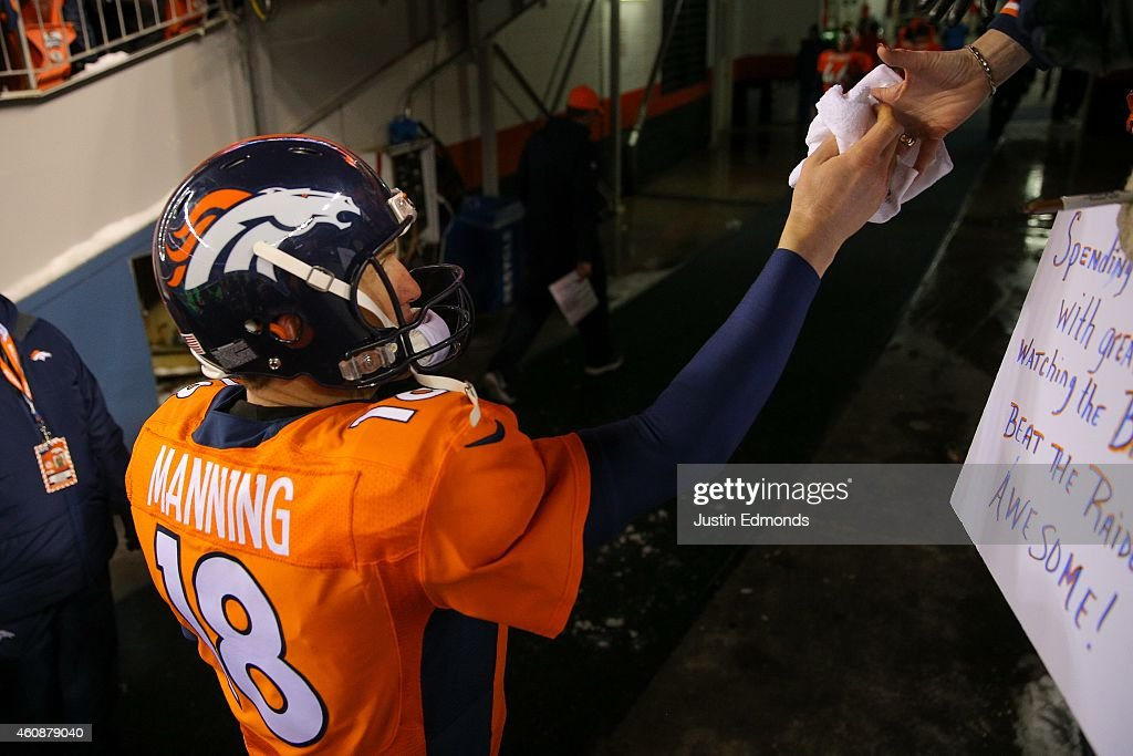 Quarterback Peyton Manning #18 of the Denver Broncos hands an item to a fan as he walks off the field after the Denver Broncos 47-14 win over the Oakland Raiders at Sports Authority Field at Mile High on December 28, 2014 in Denver, Colorado.