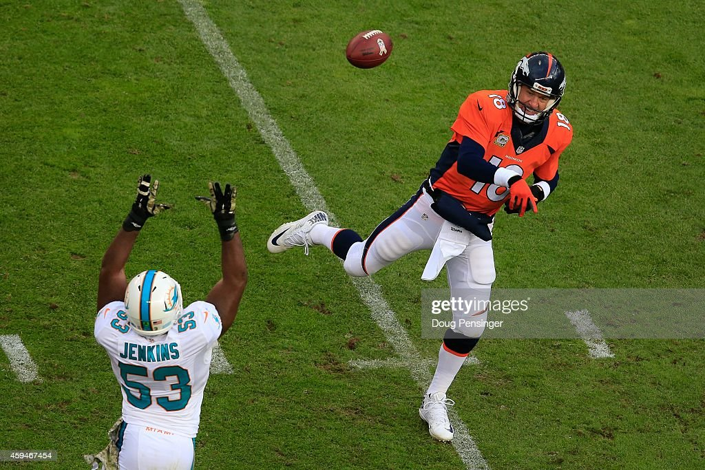 Quarterback Peyton Manning #18 of the Denver Broncos passes past outside linebacker Jelani Jenkins #53 of the Miami Dolphins int he first quarter of a game at Sports Authority Field at Mile High on November 23, 2014 in Denver, Colorado.