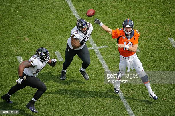 Quarterback Peyton Manning of the Denver Broncos passes under pressure by outside linebacker Terrell Suggs and defensive end Lawrence Guy of the...