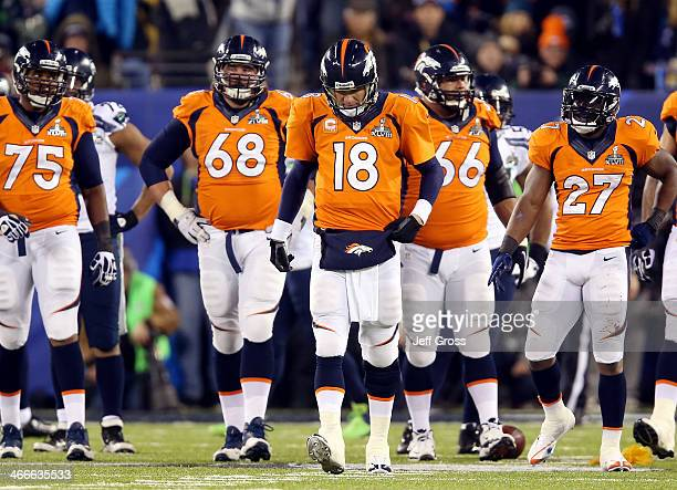 Quarterback Peyton Manning of the Denver Broncos reacts alongside teammates tackle Chris Clark guard Zane Beadles center Manny Ramirez and running...