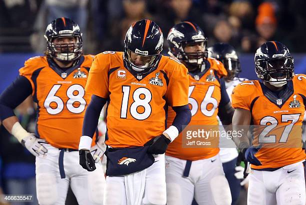 Quarterback Peyton Manning of the Denver Broncos reacts alongside teammates guard Zane Beadles center Manny Ramirez and running back Knowshon Moreno...